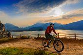 Cycling man riding on bike at sunrise mountains and Garda lake landscape. Cycling MTB enduro flow se poster