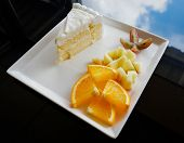 Slice Fruit And Milk Cake On White Plate / Close Up Of Fresh Orange Grape And Apple Slice On Tray Wi poster