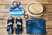 Summer Womens Clothes. Flat Lay Fashion Photo. Blue Jeans, T-shirt, Sun Hat, Blue Sandals On Wooden  poster