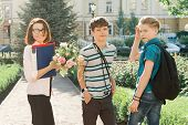Outdoor Portrait Of School Teacher With Bouquet Of Flowers And Group Of Teenage School Children. Chi poster