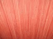 Red Background Made Of Vertical Dispersing  Bamboo Laths.