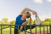 Young Woman Stretching Hand And Legs Before Her Run.woman Runner Stretching Before Workout - Outdoor poster