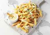 Homemade Potato French Fries With Cheese Sauce On White Wooden Board poster