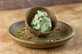 Homemade Pistachio Ice Cream Sprinkled With Pistachio Crumbs Is Served In Half A Coconut Shell. Home poster