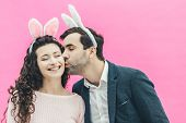 Young Tender Pair Standing On A Pink Background. During This, On The Head, A Bunny Ears. A Man Gentl poster