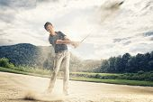 Male golf player in blue shirt and grey pants hitting golf ball out of a sand trap with sand wedge a