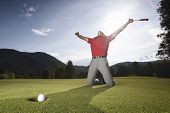 Male golf player on knees and arms raised with putter in hand in winner pose on golf green being ove
