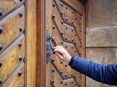 Man Holds Door Knocker From Old Wooden Door In Hand. He Knocks On The Locked Door. poster