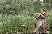 Beautiful Hippie Girl Sitting On A Stump Near The Pond. poster