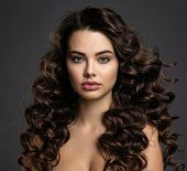 Beautiful young woman with long curly brown hair and  smoky eye makeup. Sexy and gorgeous brunette g poster