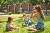 Happy Playful Children Outdoors In The Summer On Grass In A Backyard poster