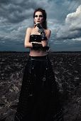 Informal Fashion: The Gorgeous Slim Young Goth Girl Dressed In Black Leather Skirt And Gloves. Outdo poster