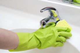 image of house cleaning  - A person cleaning the bathroom sink with a glove - JPG