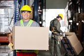 Portrait of happy mid adult foreman with cardboard box and coworker pushing handtruck at warehouse