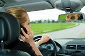 stock photo of traffic rules  - Young woman with telephone having phone conversation while driving car - JPG