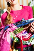 Traditional clothes - young woman is buying Tracht or dirndl in a shop, she has lots of dirndl in he