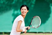 Portrait of successful tennis player with racket at the tennis court