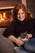Happy teenage girl sitting at fireplace at home fondling cat smiling.