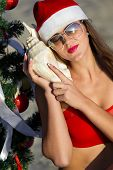 Sexy Santa's helper  listening to the sea by a seashell next to the Christmas tree at the tropical beach