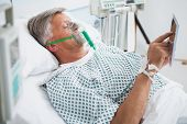 Patient is lying in bed reading wearing an oxygen mask in hospital ward