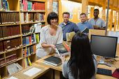 picture of librarian  - Librarian handing book to woman at library desk - JPG