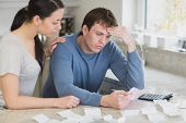 Worried couple looking over bills in kitchen