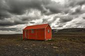 Old red snowstorm shelter can save a life in a cruel blizzard or in winter on Iceland