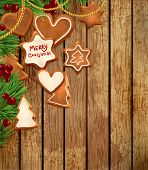 Gingerbread cookies with Christmas tree branches and Holly berries. Wood background. Old texture for