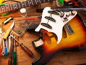 Sunburst electric guitar on guitar repair desk or in a repair work shop. Neck and pickguard detached