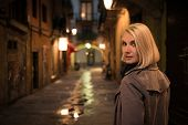Beautiful blond woman in raincoat walking alone outdoors at night