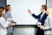 Confident businessman pointing at whiteboard while making speech at meeting