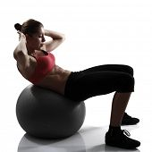 sport girl doing abs press exercise with fitness ball, silhouette studio shot over white background