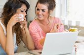 Girls chatting over coffee with laptop in kitchen