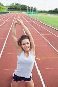 Happy woman stretching her arms on a track