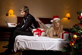 Young woman in Santa's hats  with glass of champagne lying on bed remain all alone because her boyfr