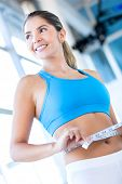 Gym woman measuring her waist and smiling