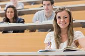 stock photo of hall  - Students sitting at the lecture hall while smiling and taking notes - JPG