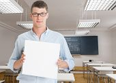 Young man holding a blank board in a classroom