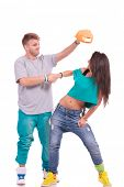 hip hop couple, man trying to put his hat on the woman's head while shaking hands...goofing around o
