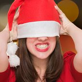 angry woman with a christmas hat covering her eyes against an abstract background