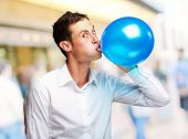 Portrait Of Young Man Blowing a�?� Balloon, Outdoor