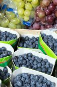 Fresh blueberries and grapes on display at a greengrocer