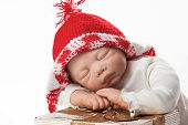 stock photo of baby doll  - Christmas Baby Doll Boy with Knit Cap sleeping on Gift Box - JPG