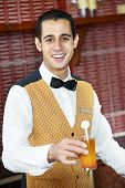 Cheerful arab barman in uniform with cocktail in his hand