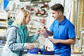 stock photo of hardware  - Assistant seller help buyer by demonstrating paint roller for painting at hardware store - JPG
