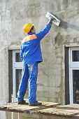 builder worker plastering facade industrial building with putty knife float