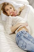 Beautiful and attractive young adult smile blonde woman posing in blue jeans and grey sweater on the white sofa