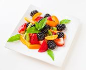 picture of dessert plate  - Fruit salad with fresh strawberries blackberries kiwis and kumquats on a plate on light background - JPG