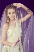 Portrait of a beautiful bride with long curly hair wearing lace dress over shorts standing under tul