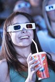 Closeup of a beautiful young woman drinking soft drink while watching a 3D movie in the theatre